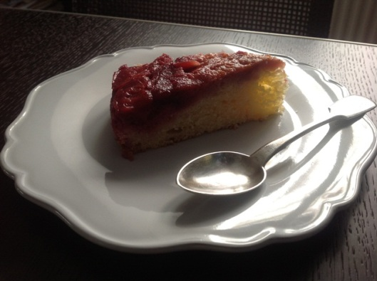side view of plum cake and spoon with light falling on to it