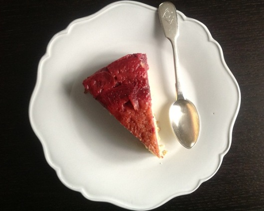 upside down plum cake on pretty white plate with antique silver spoon