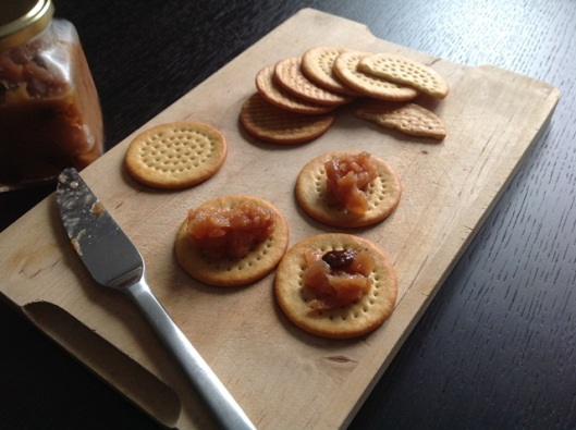 Quince chutney with cheese crackers on a bread board