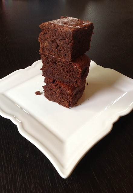 a stack of beetroot brownies on a pretty white plate with pointy corners