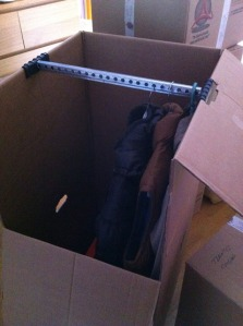 a cardboard box with a rack for hanging clothes