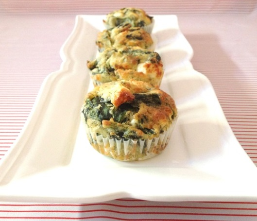 A row of spanakopita muffins lined up on a pretty plate, placed on a red and white striped table cloth