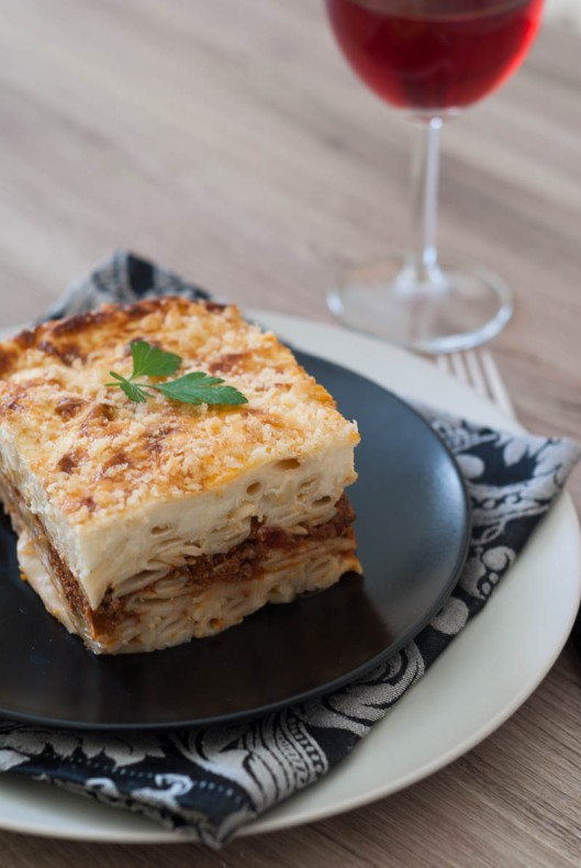 A piece of pastitsio with a glass of red wine
